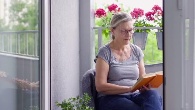 vidéos et rushes de femme aîné s'asseyant obalcony pendant l'isolement - 60 64 ans