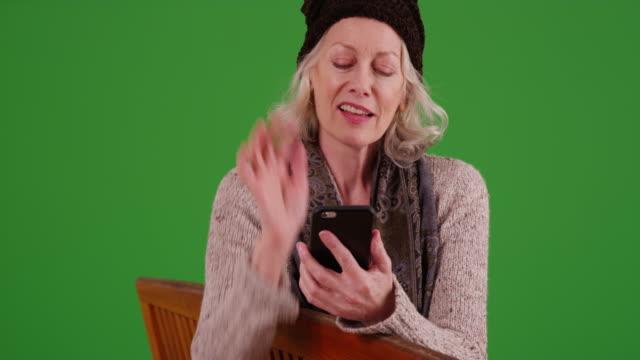 vídeos de stock, filmes e b-roll de senior woman sitting on bench messaging on cellphone on greenscreen - smart
