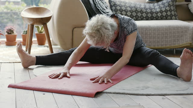 senior woman sitting on floor leaning forward in yoga session - serene people stock videos & royalty-free footage