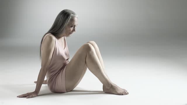 vídeos y material grabado en eventos de stock de senior woman sitting on floor - camisola