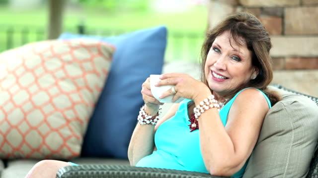 vidéos et rushes de haute femme assise sur le canapé de patio - jeune d'esprit