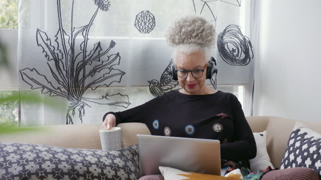 senior woman sitting on sofa using laptop - content stock videos & royalty-free footage
