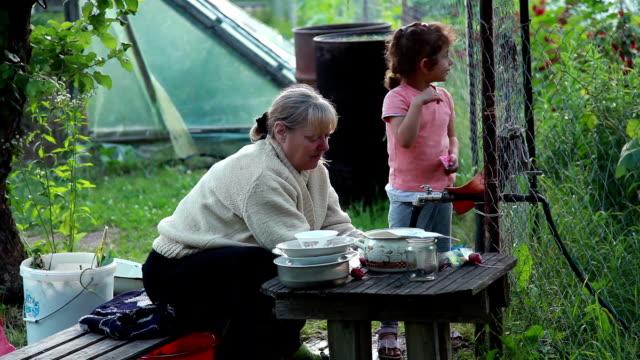 vidéos et rushes de haute femme assis sur le banc et laver la vaisselle sous le robinet d'eau dans l'arrière-cour - clôture jardin