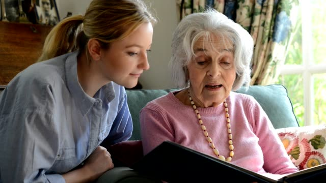 senior woman sitting with adult granddaughter at home looking through photo album together - terza età video stock e b–roll