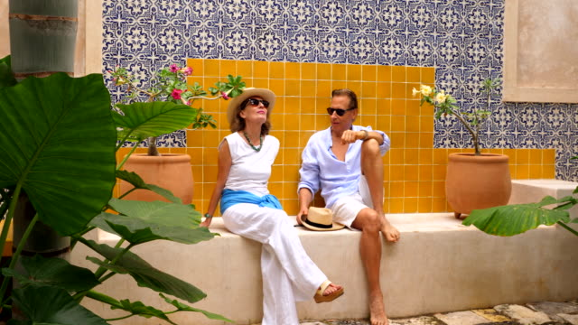 ms senior woman sitting with husband in tropical spa garden while on vacation - cross legged stock videos & royalty-free footage