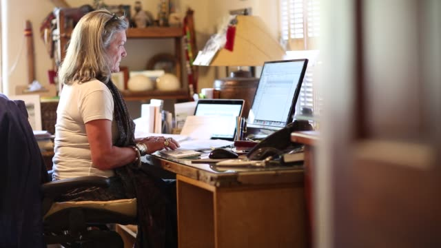 Senior woman small business owner typing on her desktop computer