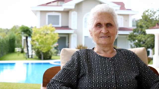 senior woman smiling and looking at camera. retired old woman with white hair sitting outdoor in a sunny summer day - white hair stock videos & royalty-free footage