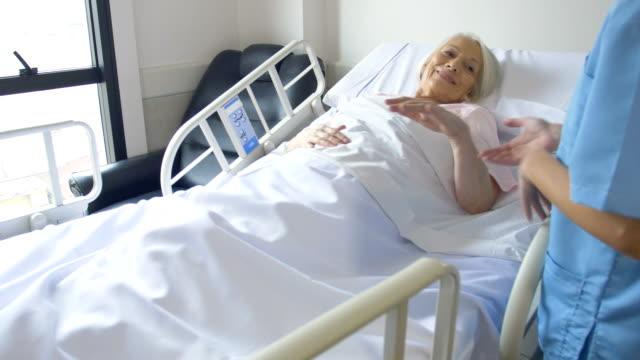 ältere frau lächelnd an krankenschwester im krankenhaus - heilbehandlung stock-videos und b-roll-filmmaterial