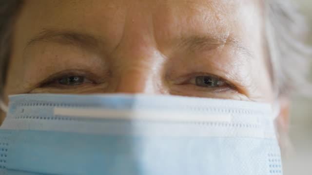 stockvideo's en b-roll-footage met hogere vrouw die achter het masker glimlacht - operatiemasker