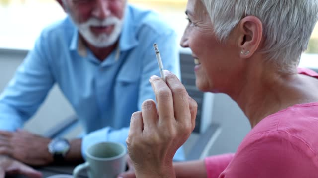 senior woman smoking while relaxing outdoors with her husband - cigarette stock videos & royalty-free footage