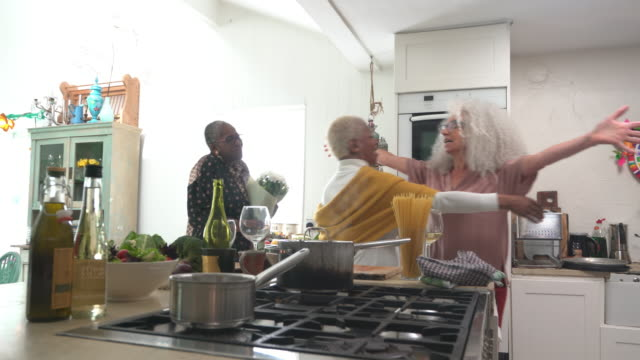 Senior woman social gathering around kitchen Island in modern house.