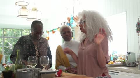 senior woman social gathering around kitchen island in modern house. - preparing food stock videos & royalty-free footage
