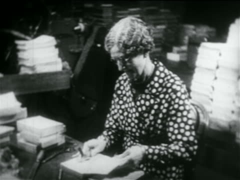 stockvideo's en b-roll-footage met b/w 1934 senior woman stamping books in library in wpa project / documentary - alleen één oudere vrouw