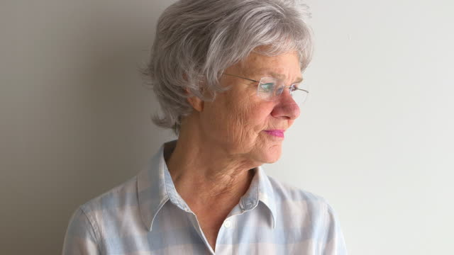 senior woman standing by white wall - one senior woman only stock videos & royalty-free footage