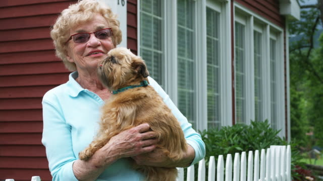 MS Senior woman standing in front of house and holding dog, smiling / Manchester, Vermont, USA.