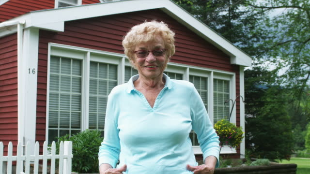 ms senior woman standing in front of house and smiling / manchester, vermont, usa. - in front of stock videos & royalty-free footage