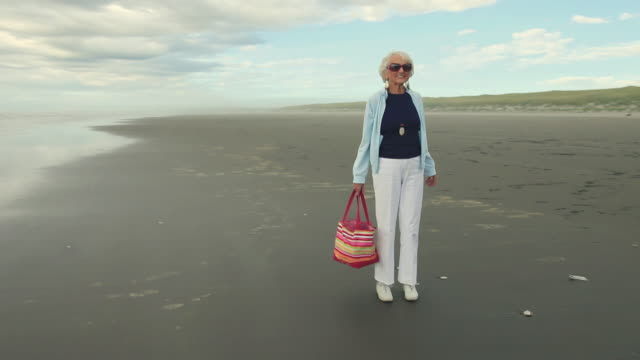 ws ds senior woman standing on beach / portland, oregon, usa - stare in piedi video stock e b–roll