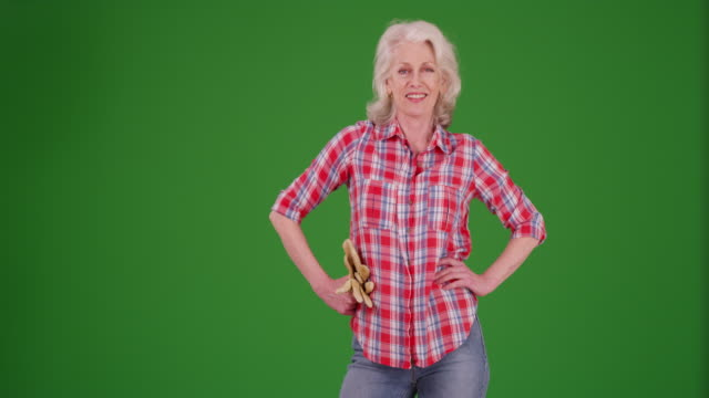 senior woman standing with hands on hips holding gardening gloves on greenscreen - gardening glove stock videos & royalty-free footage