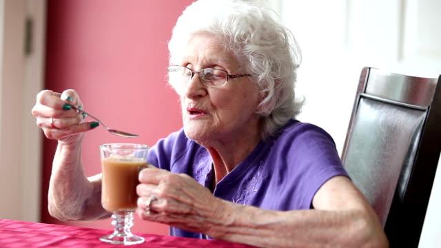 Senior vrouw roeren en nippende thee
