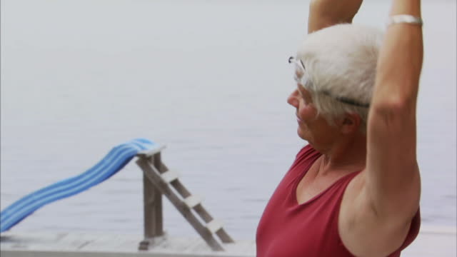 ms portrait senior woman stretching and turning to camera smiling / waverly, nova scotia, canada - swimwear stock videos and b-roll footage