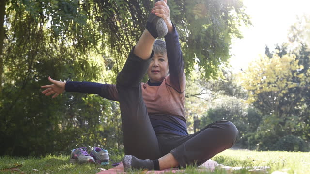 vidéos et rushes de senior woman stretching in park - souplesse