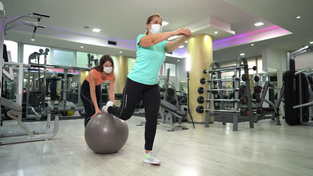 senior woman stretching with trainers help - sportswear stock videos & royalty-free footage