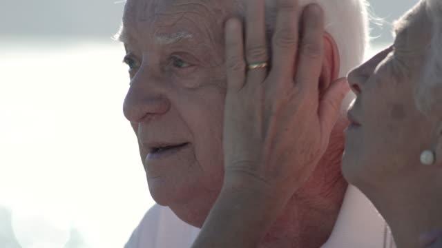 vidéos et rushes de senior woman stroking her husband's face with love and affection - caresser