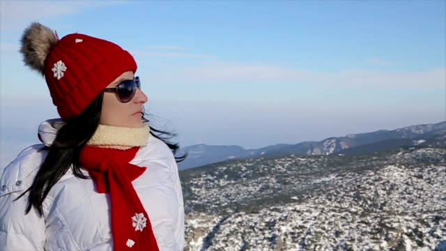 Senior woman sunbathing on the mountain at winter