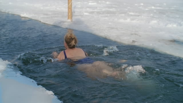 senior woman swimming in ice-hole - kälte stock-videos und b-roll-filmmaterial