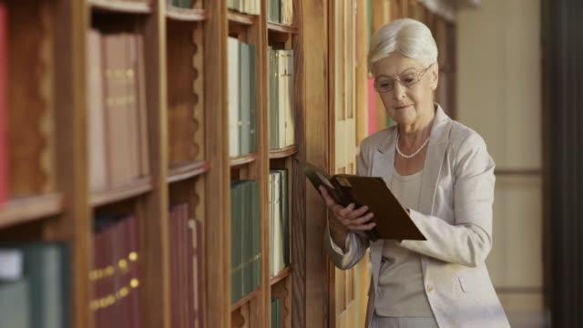 TU Senior mujer tomando un libro en la biblioteca de estante