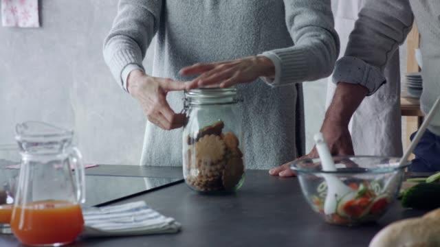 stockvideo's en b-roll-footage met senior vrouw het nemen van peperkoek koekjes uit een koektrommel - glazen pot