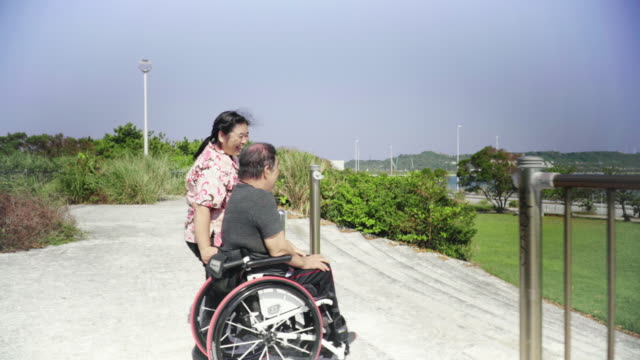 senior woman taking her husband, who is in a wheelchair, for a walk in a park - 介護点の映像素材/bロール