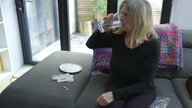 senior woman taking her medication - senior women stock videos & royalty-free footage
