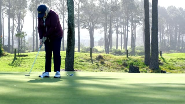 senior woman taking her putt on the putting green - putting green stock videos and b-roll footage