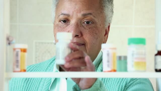 cu senior woman taking over the counter medicine bottle from medicine cabinet / richmond, virginia, usa - prescription medicine bottles stock videos & royalty-free footage