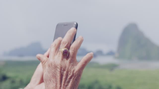スマートフォンで写真を撮る4kシニアウーマン - 年配の女性点の映像素材/bロール