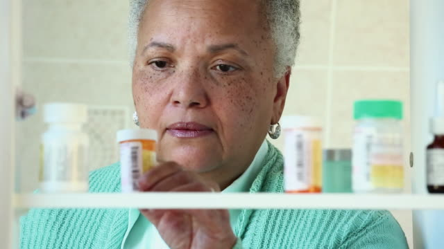 cu senior woman taking prescription bottle from medicine cabinet / richmond, virginia, usa - prescription medicine stock-videos und b-roll-filmmaterial