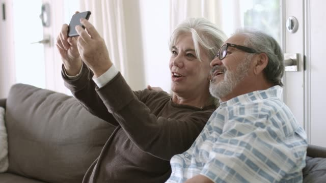 senior woman taking selfie with husband at home - 60 64 years stock videos & royalty-free footage