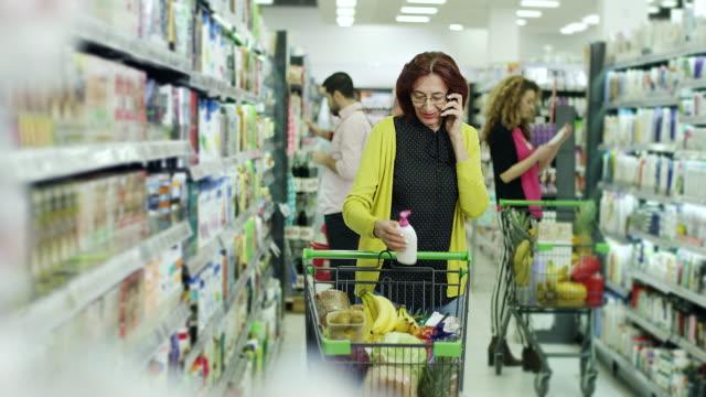 スーパー マーケットで電話で話している年配の女性 - 食料品点の映像素材/bロール