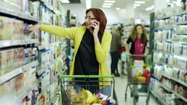 Senior woman talking on phone in supermarket