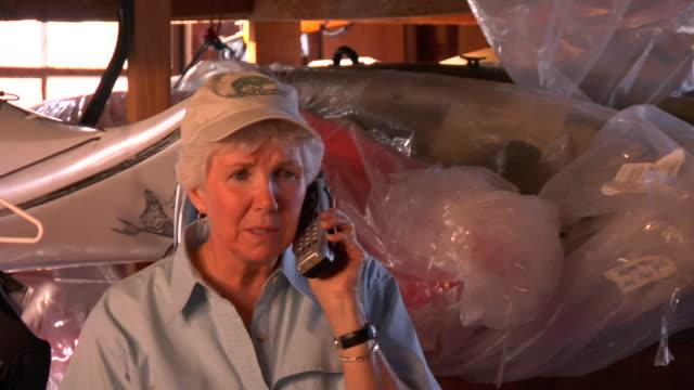 vidéos et rushes de cu, senior woman talking on phone, kayaks in background, st. simons, glynn county, georgia, usa - téléphone sans fil