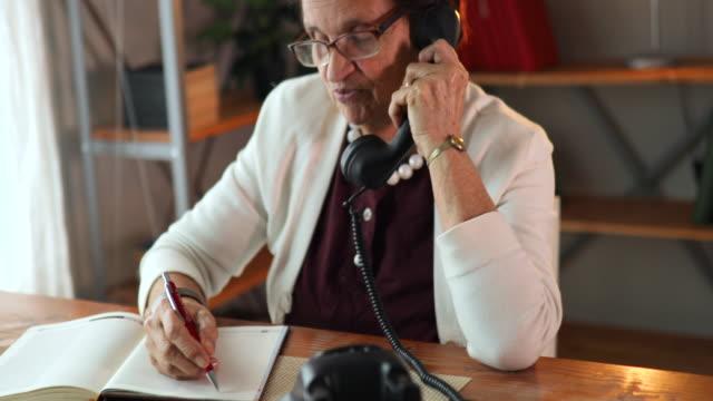 stockvideo's en b-roll-footage met senior vrouw praten over de telefoon thuis. - vaste telefoon