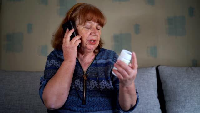 vídeos de stock, filmes e b-roll de mulher idosa falando ao telefone e segurando um frasco de pílulas - só uma mulher madura