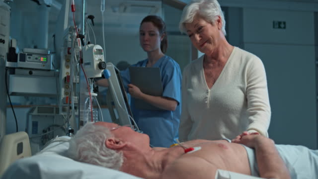 Senior woman talking to her husband lying in the ICU after surgery