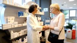 Senior woman talking while shaking hand of chemist