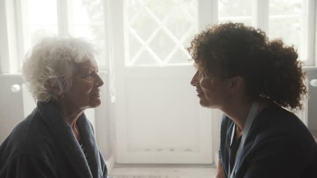 senior woman talking with female caregiver - bathrobe stock videos & royalty-free footage