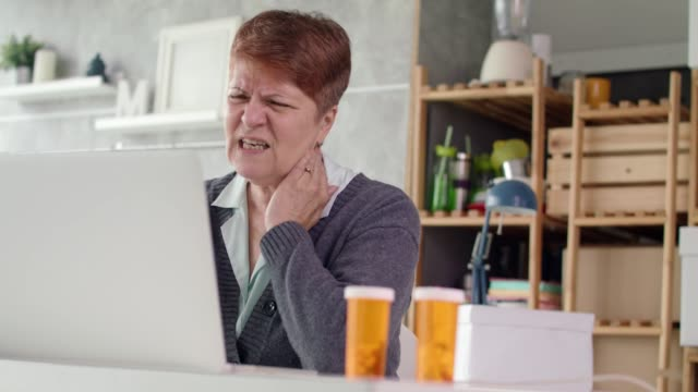 senior woman talking with her doctor over the internet - neckache stock videos & royalty-free footage