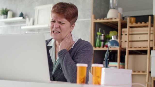 vídeos de stock e filmes b-roll de senior woman talking with her doctor over the internet - dor no pescoço