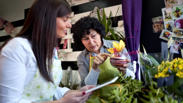 senior woman teaching a young woman the art of flower decoration - fioraio negozio video stock e b–roll