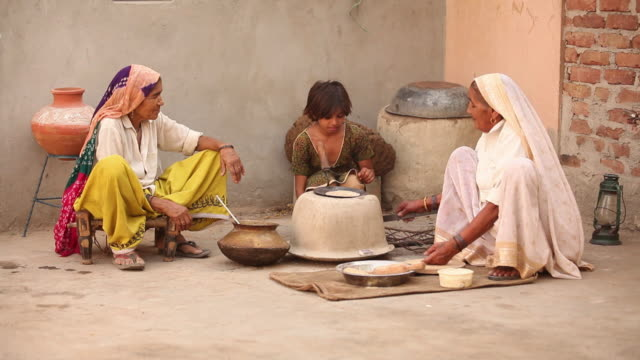 Senior woman teaching her granddaughter to cook, Faridabad, Haryana, India